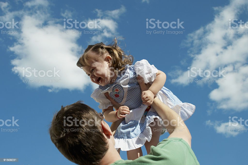 father with her baby playing outdoor against the sky royalty-free stock photo