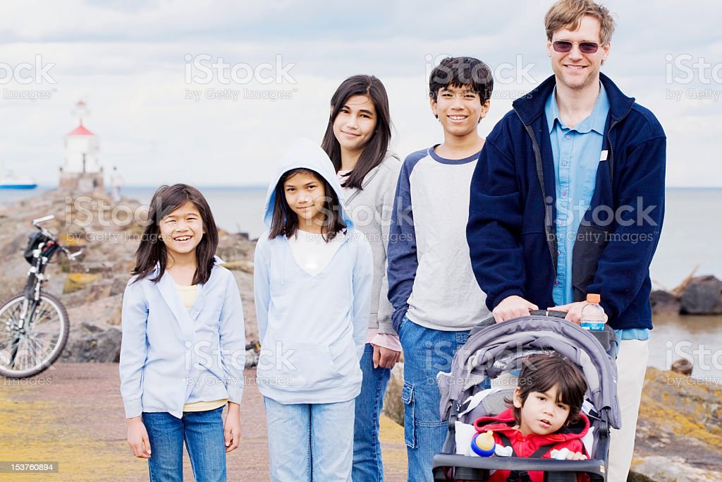 Father with his five children at the beach stock photo