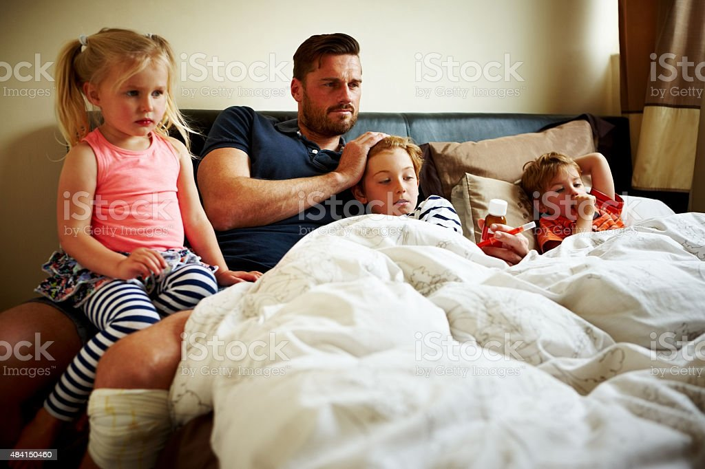Father with his three children on bed looking away stock photo