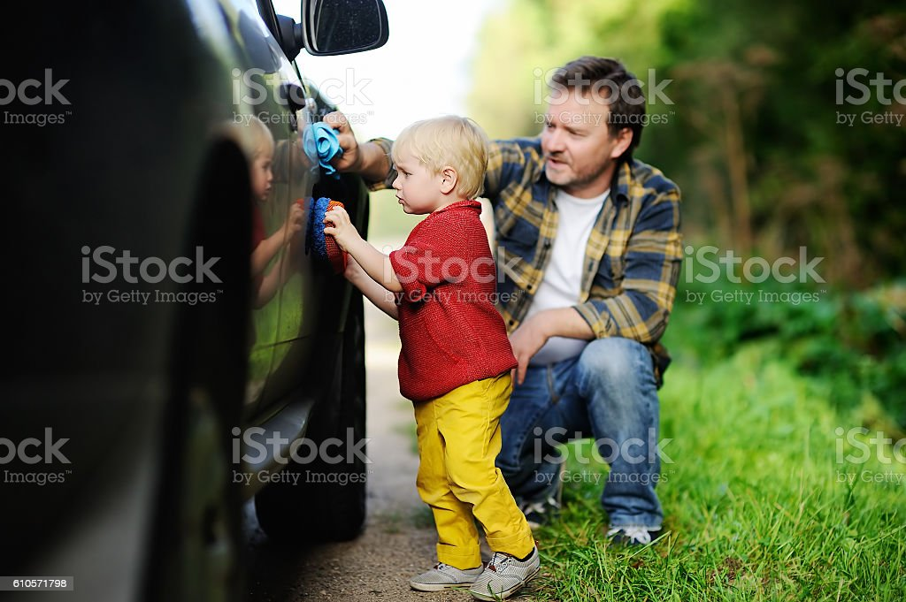 Father with his toddler son washing car together stock photo