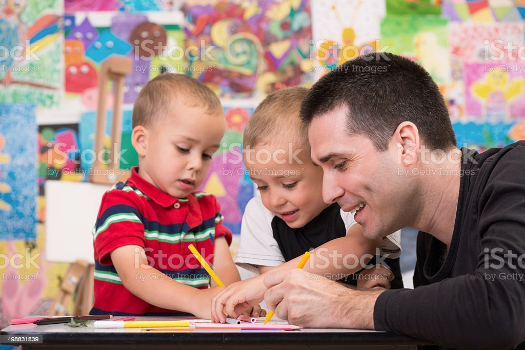 Father with his two sons enjoys painting stock photo