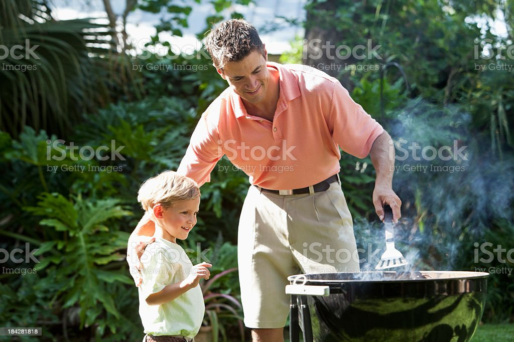 Father with little boy cooking on barbecue grill royalty-free stock photo