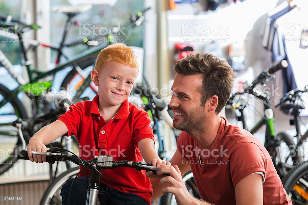 Father with little son in bike store stock photo