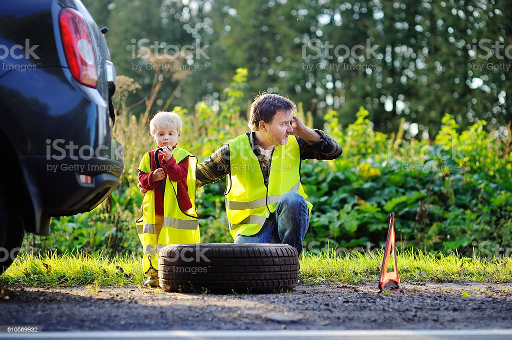Father with little son repairing car and changing wheel together stock photo