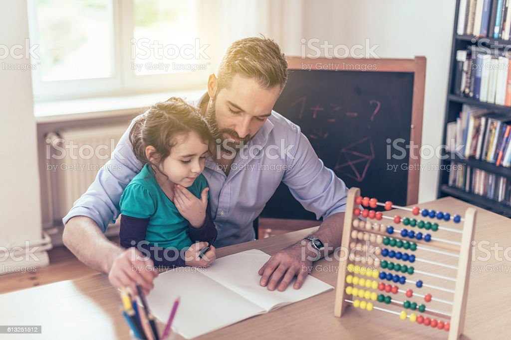 father with pre-scholar girl learning for school at home stock photo
