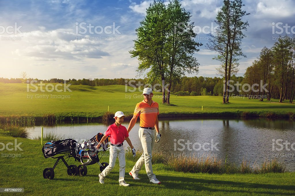 Father with son at golf field stock photo
