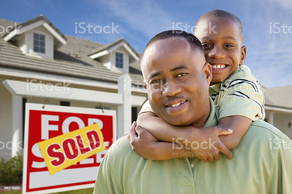 Father with Son In Front of Sold Sign and Home stock photo