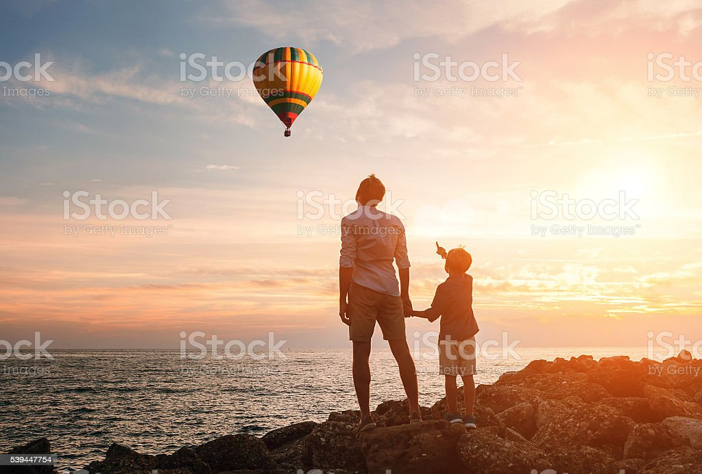 Father with son look on the balloon on the sea coast stock photo