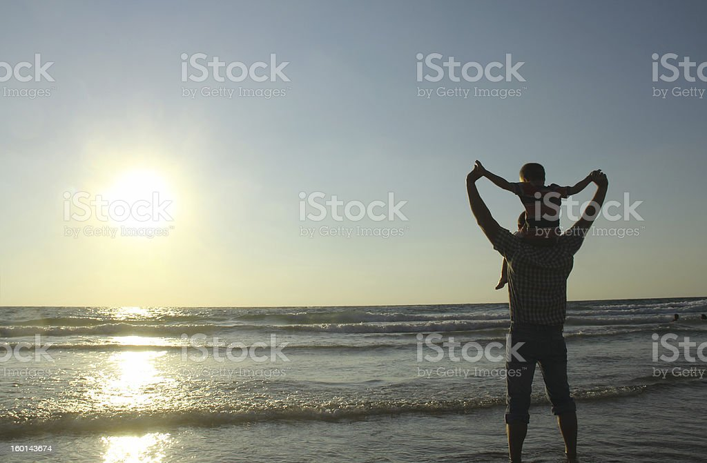 Father with son on shoulders at the beach  stock photo