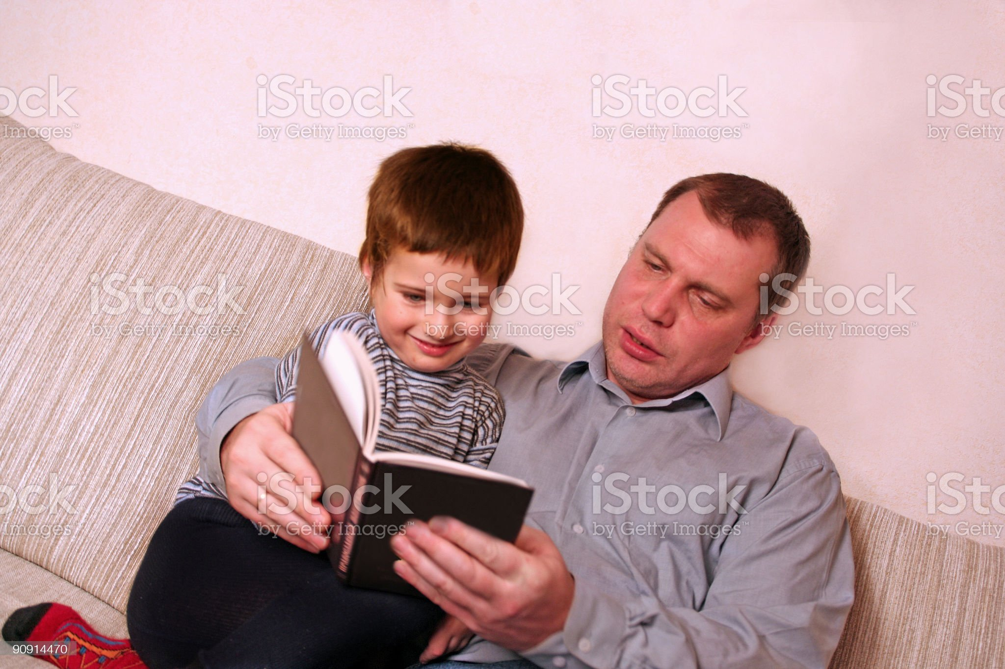 father with  son they read  book on  sofa royalty-free stock photo