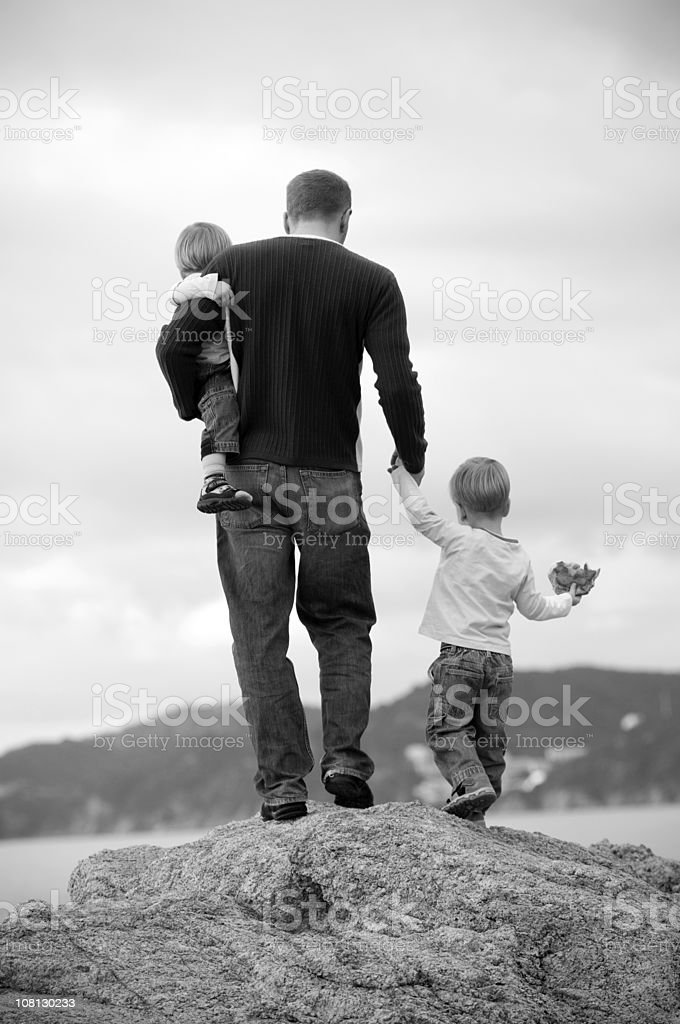 Father with Sons Climbing Rocks Near Ocean, Black and White royalty-free stock photo