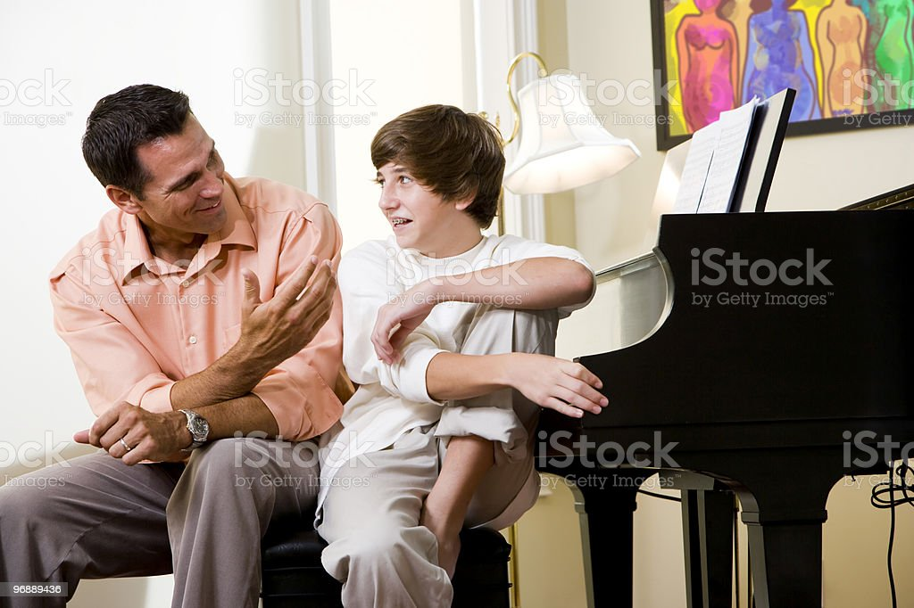 Father with teenage son at home smiling stock photo