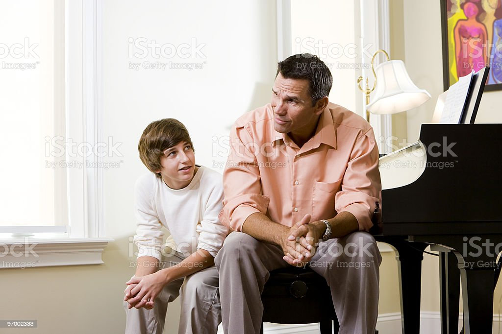 Father with teenage son sitting together at home conversing royalty-free stock photo