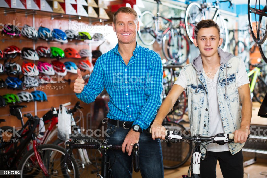 Father with teenager trying new bicycle stock photo