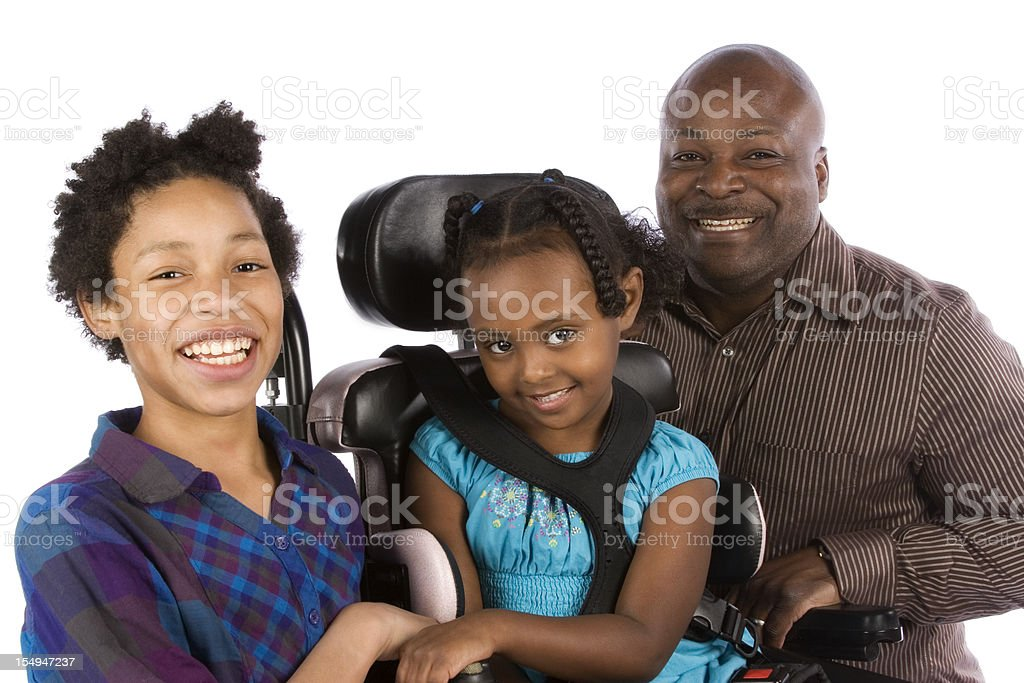 Father with two daughters, one in a wheel chair stock photo