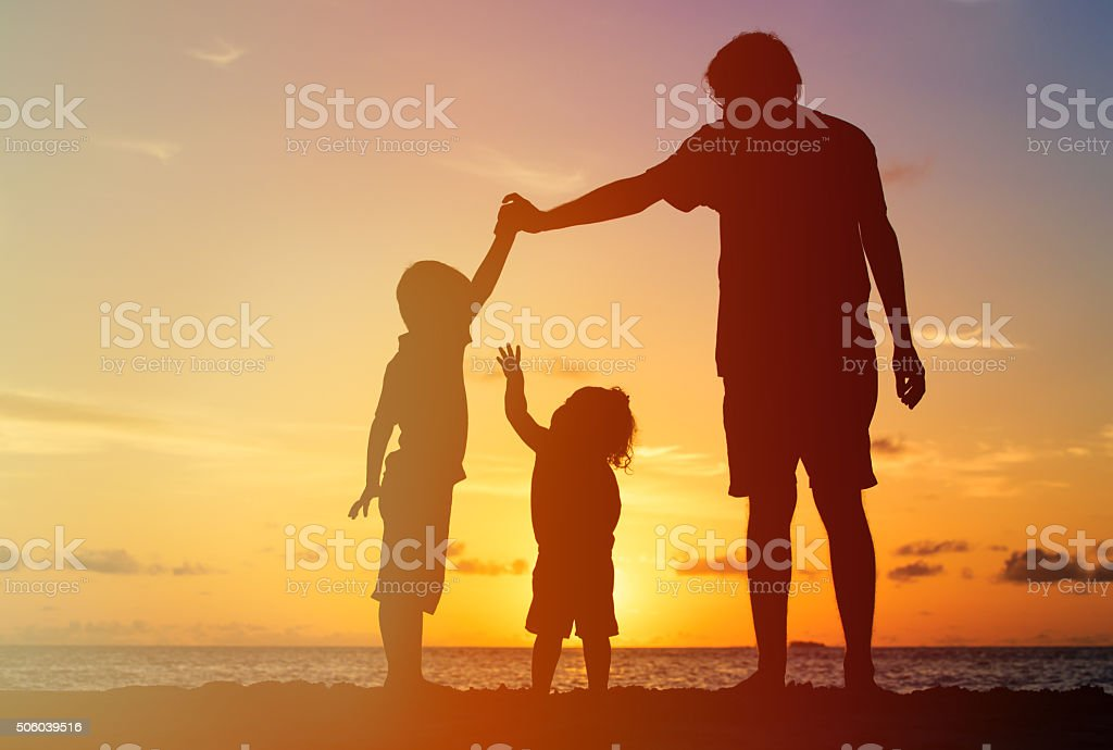 father with two kids, boy and girl, playing at sunset stock photo