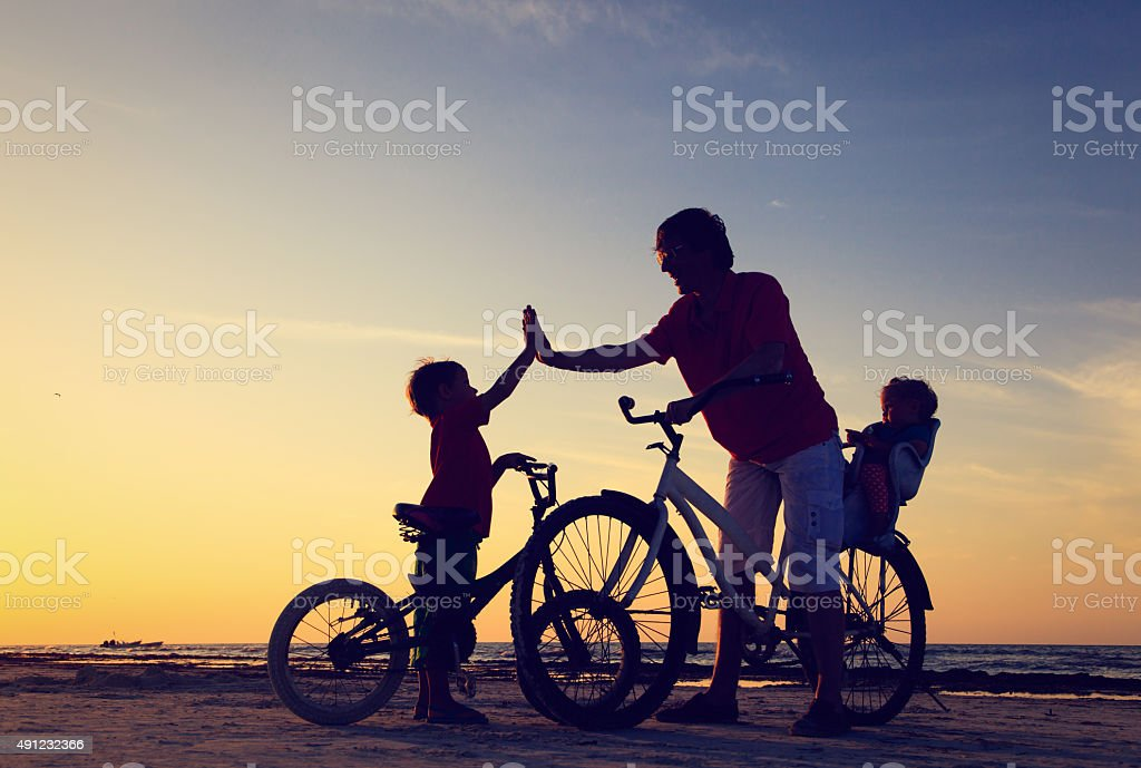 father with two kids on bikes at sunset stock photo