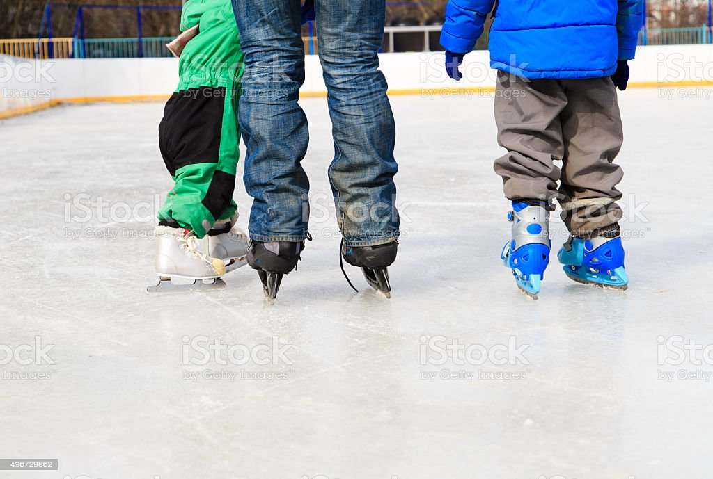 father with two kids skating in winter stock photo