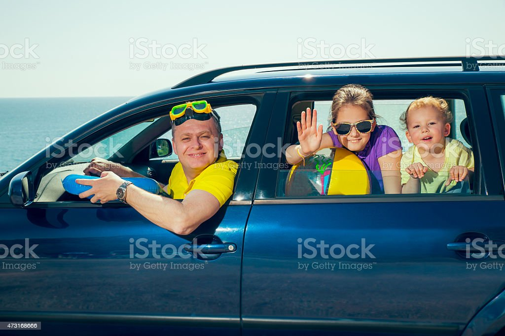 Father with two kids travel by car on sea vacation stock photo