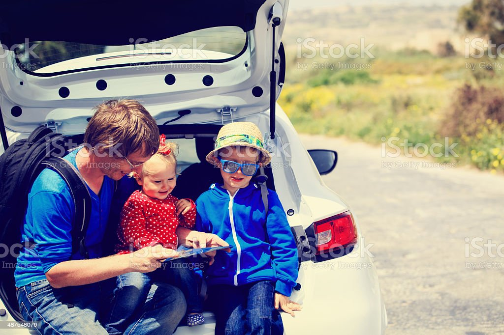 father with two kids travel by car stock photo