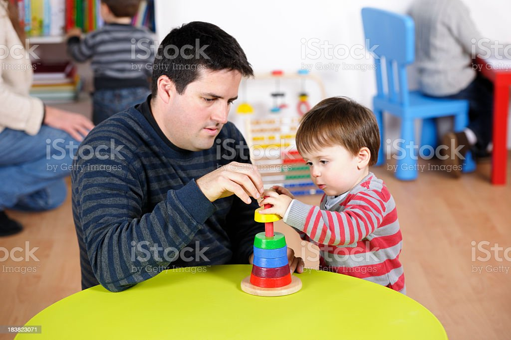 Father/Carer/Childminder Encourage Toddler During Playtime stock photo
