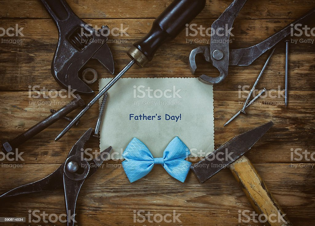 Fathers Day card, old tools on wooden table, sheet of paper, blue bow