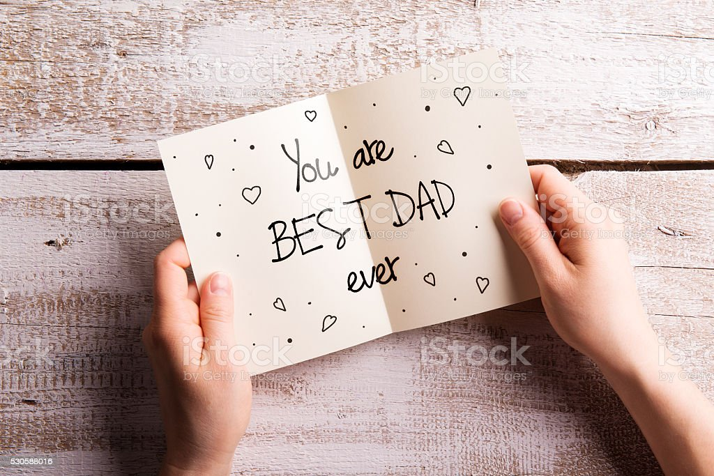 Fathers day composition. Hands of dad holding greeting card stock photo