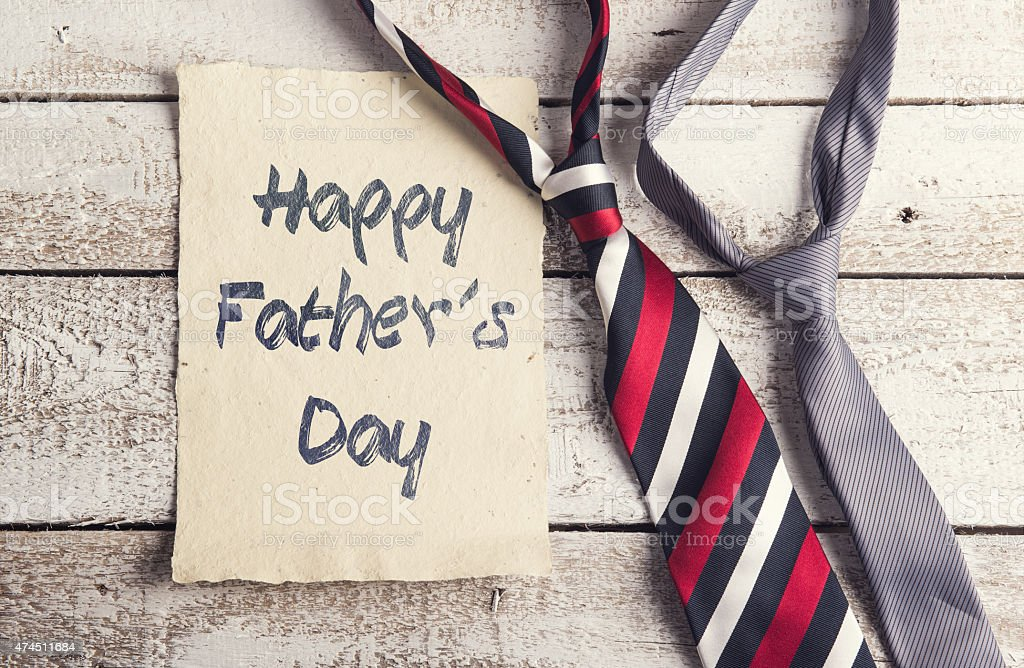 Happy fathers day sign on paper and colorful ties laid on wooden...