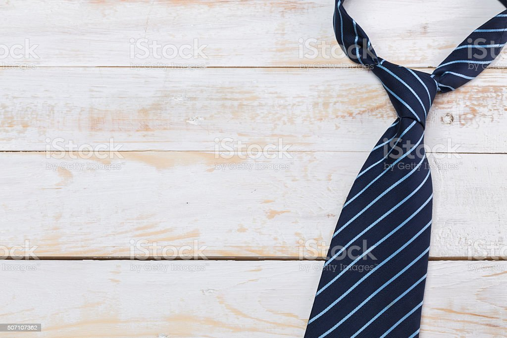 Fathers day composition, tie laid on wooden floor. stock photo