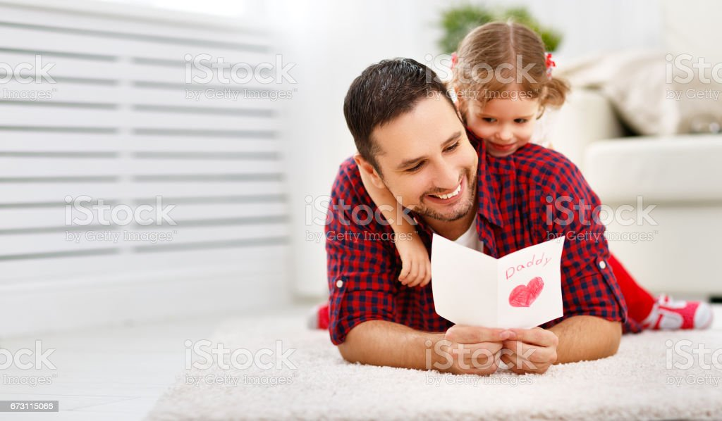 Father's day. Happy family daughter giving dad greeting card stock photo