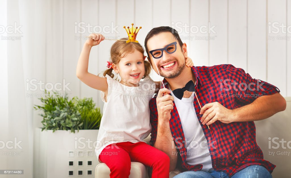 Father's day. Happy family daughter in crown hugging dad and laughs stock photo