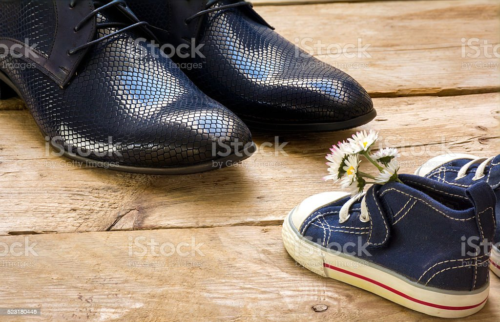 father's day, small kids sneakers with daisies and men's shoes stock photo