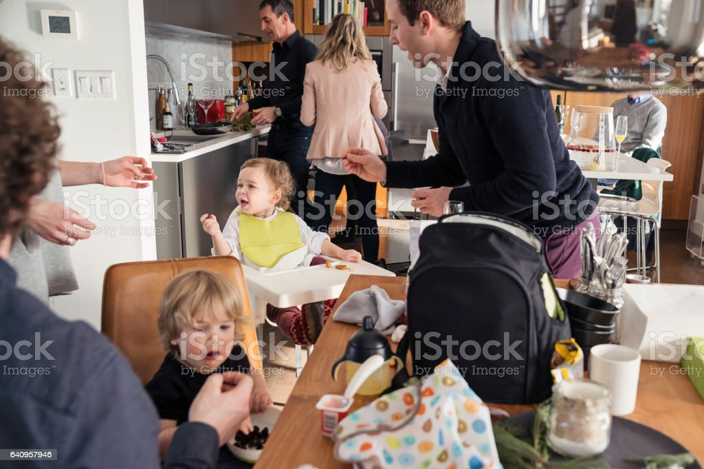 Fathers feeding toddlers before big family dinner, lots of action. stock photo