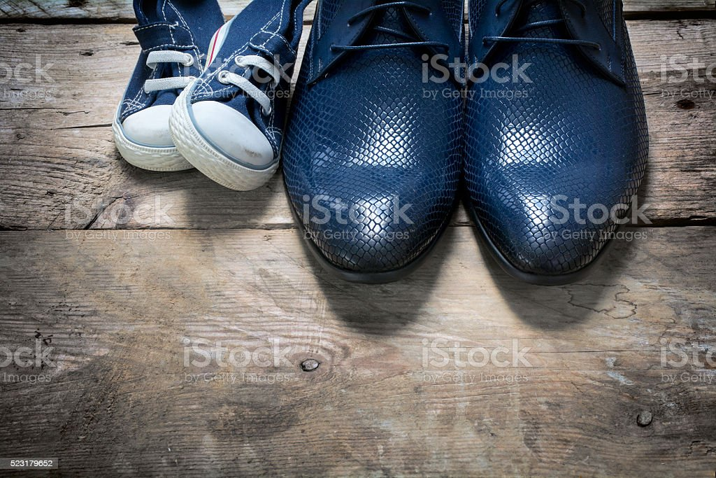 father's  shoes and kids sneakers side by side, father's day stock photo