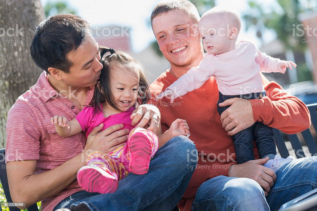 Fathers sitting outdoors with children on bench stock photo