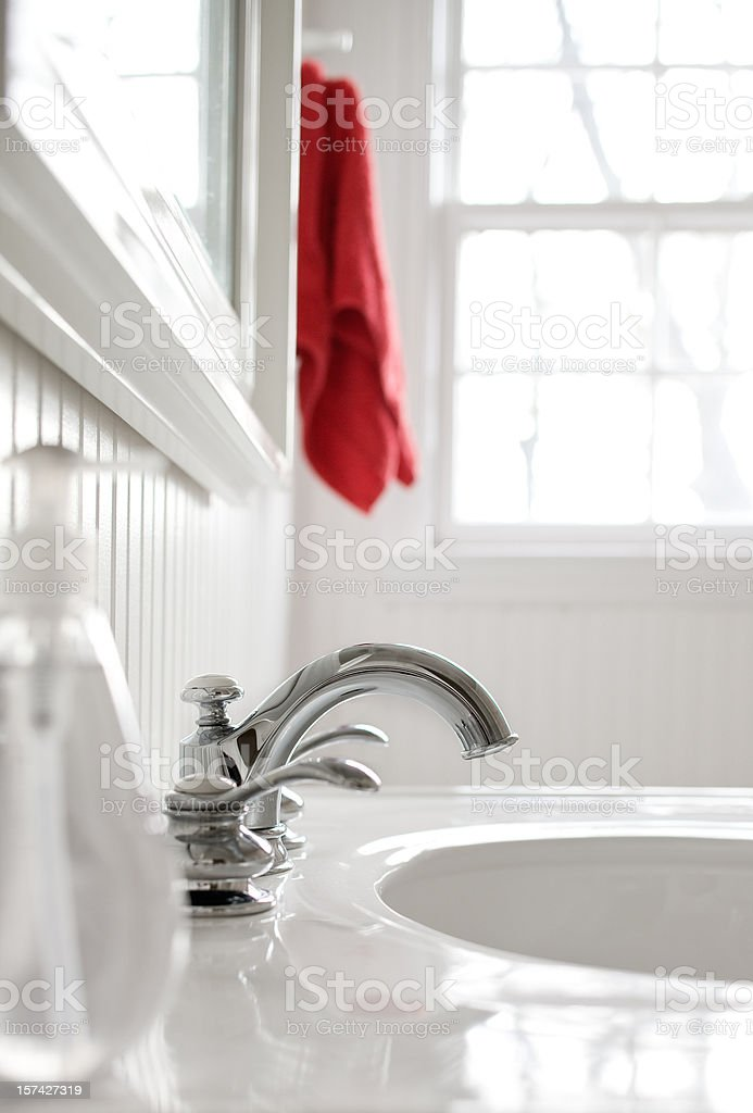 Faucet in  white bathroom with a red towel. stock photo