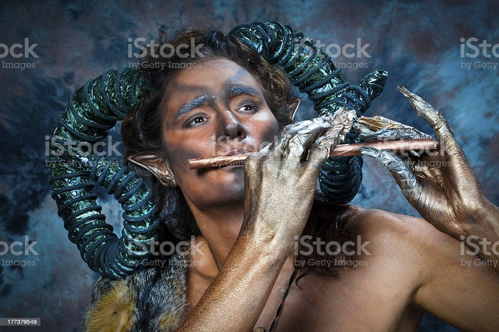 Faun playing the flute stock photo