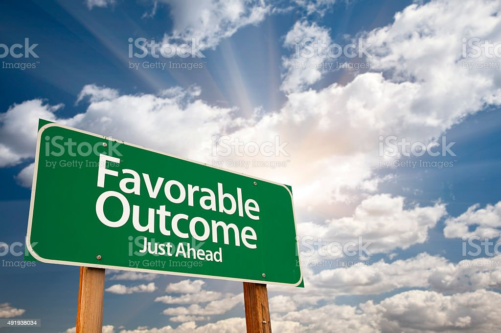 Favorable Outcome Green Road Sign Over Clouds stock photo