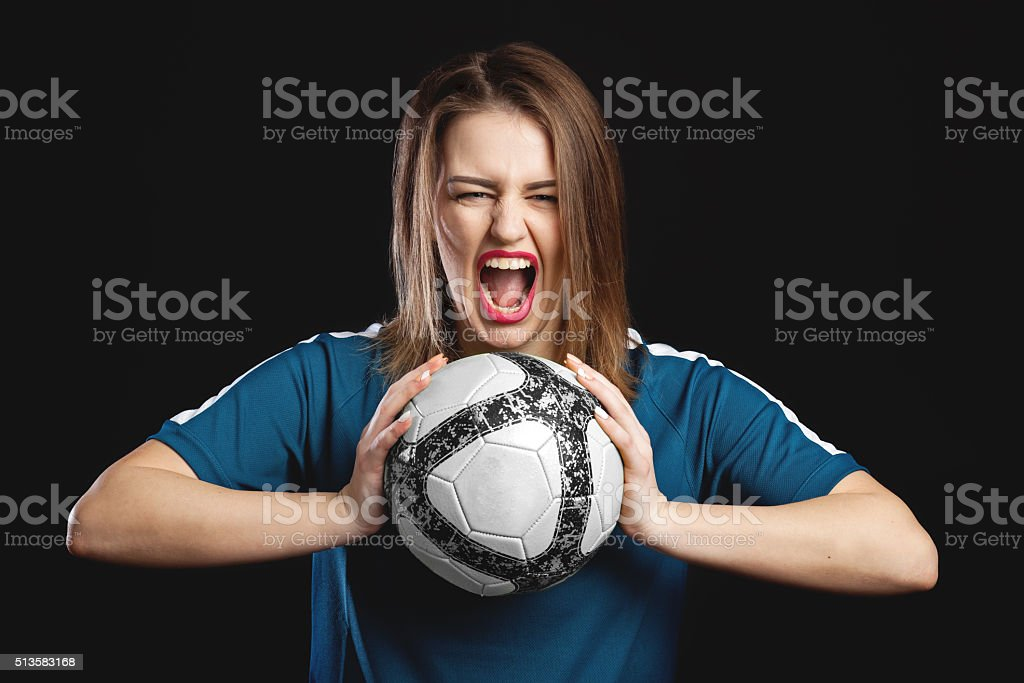 feamel soccer player screaming with soccer ball in hands stock photo