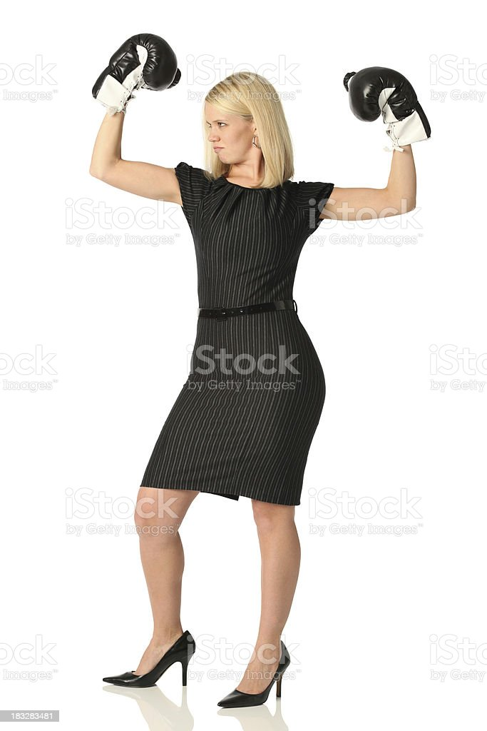 Fearless businesswoman wearing boxing gloves and flexing royalty-free stock photo