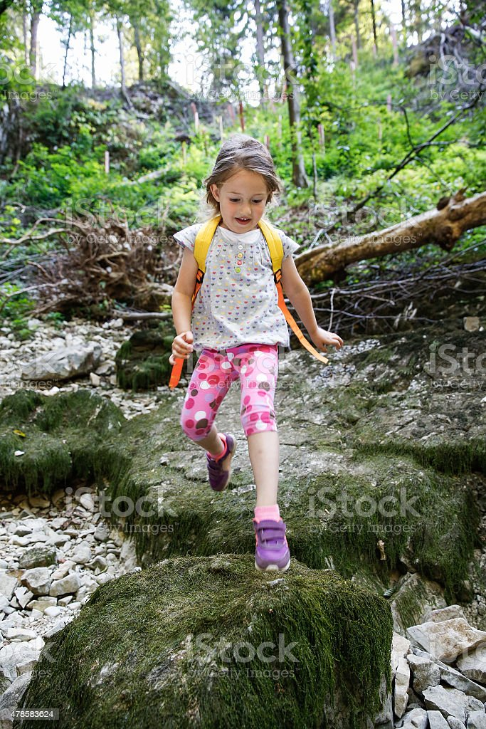 Fearless little girl scout jumping over stones stock photo