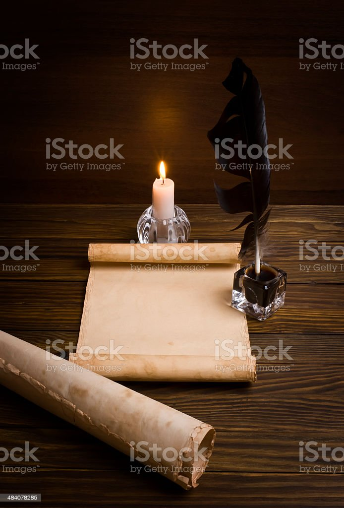 feather, old paper and candle on a wooden background stock photo