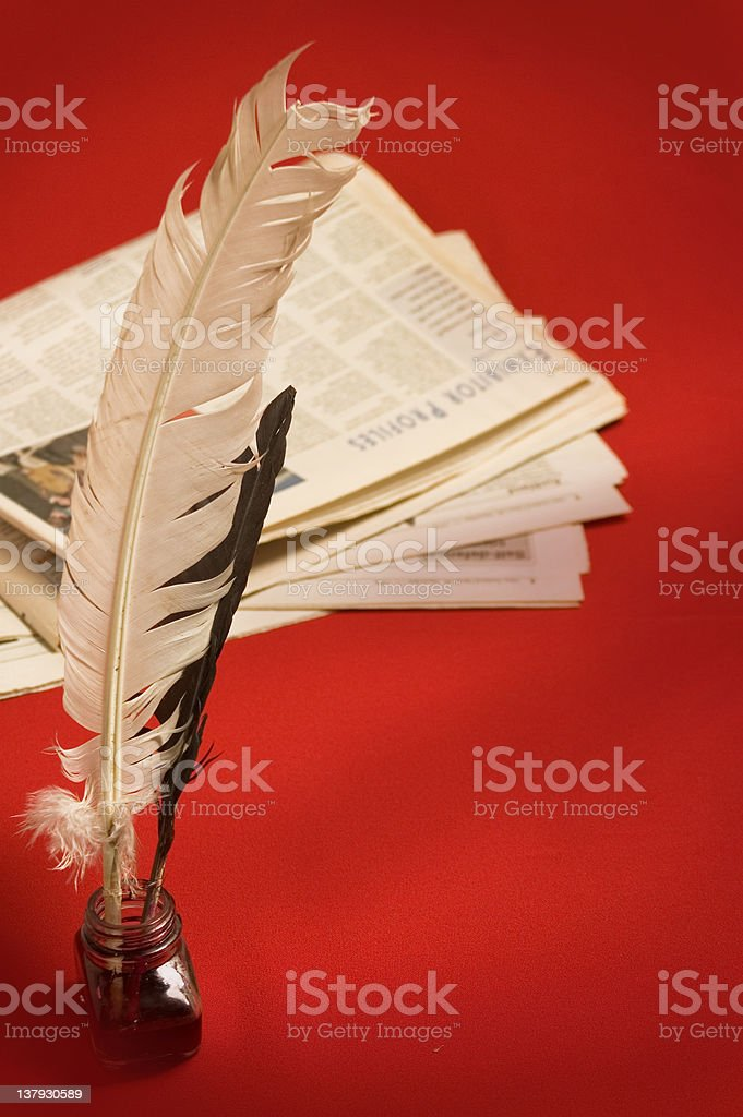 Feather quill and newspapers royalty-free stock photo