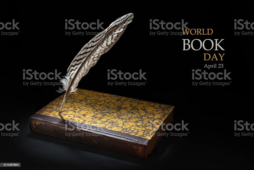 Feather standing on a book against black, world book day stock photo