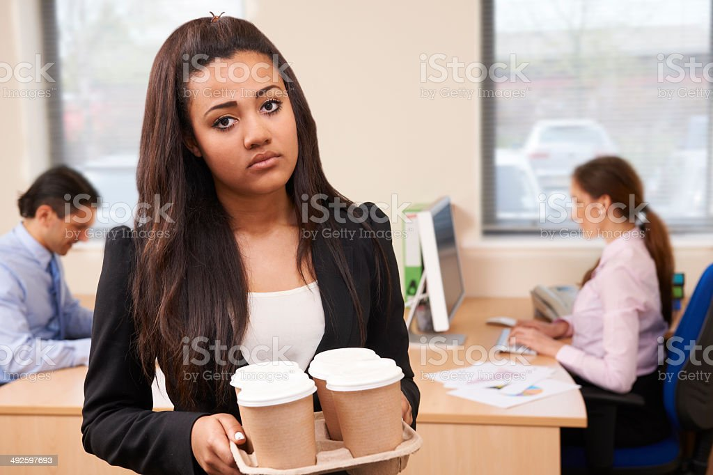 Fed Up Female Intern Fetching Coffee In Office stock photo