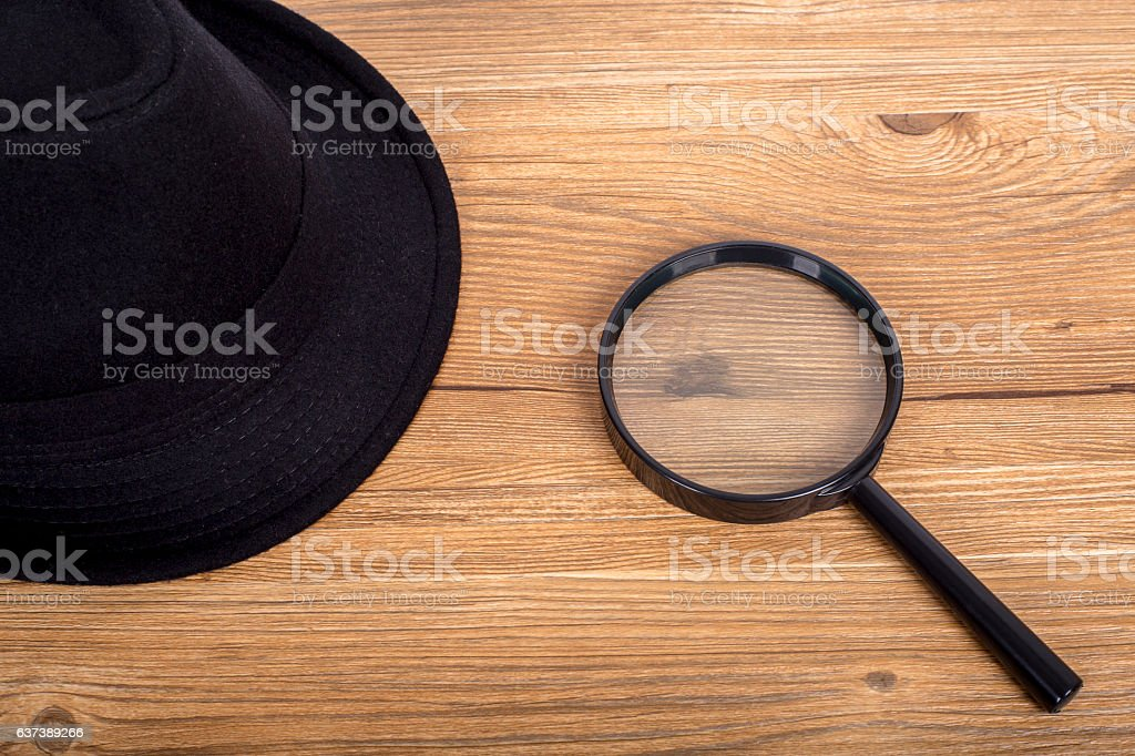 fedora hat and a magnifier on table stock photo