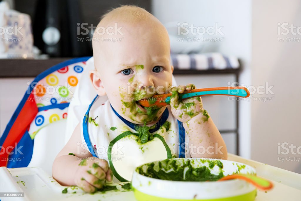 Feeding. Baby's first solid food stock photo