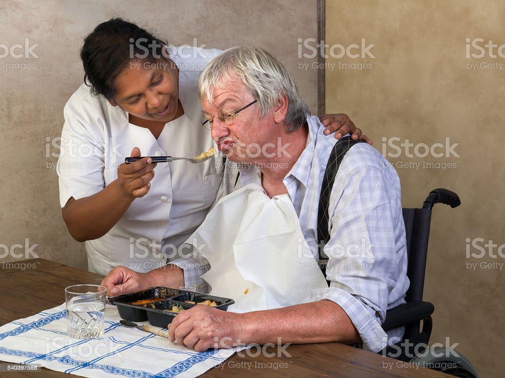 Feeding elderly man stock photo