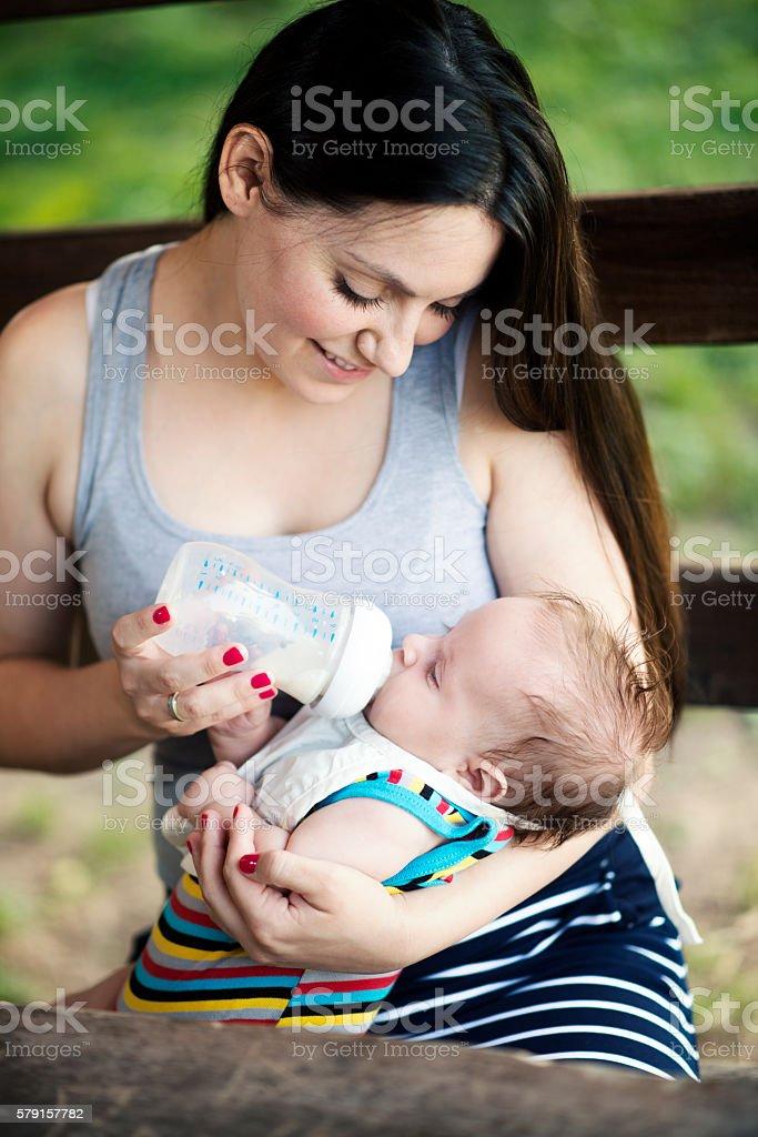 Feeding pretty baby outdoors stock photo