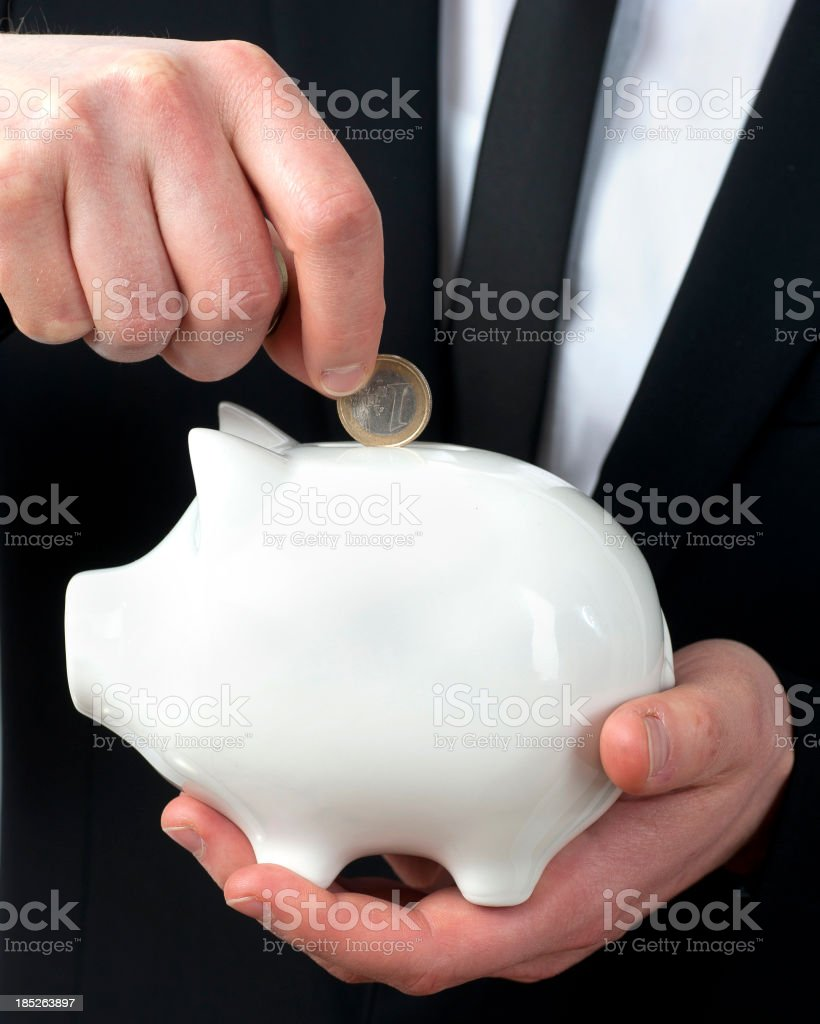 feeding the piggy bank - vertical royalty-free stock photo